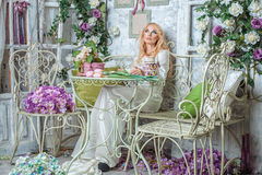 The girl in the room with flowers. Beautiful young blond woman sitting in the room with flowers Stock Photo