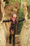 Girl on rope bridge. Young girl on swinging rope bridge with green background stock photos