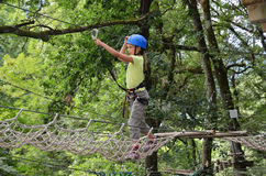Girl in the rope parkour. Preteen girl is climbing on the rope net at the ropes course. She is photographed on the high tree in the green forest Stock Images