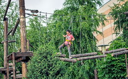 Girl on the ropes course attraction. The girl goes on ropes on a rope attraction in Almaty Royalty Free Stock Images