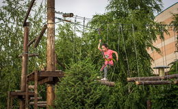 Girl on the ropes course attraction. The girl goes on ropes on a rope attraction in Almaty Stock Image