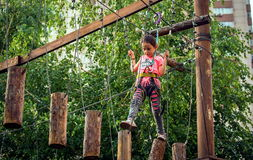 Girl on the ropes course attraction. The girl goes on ropes on a rope attraction in Almaty Royalty Free Stock Image