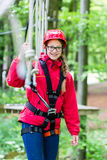 Girl roping up in high rope course Stock Images