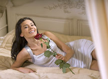 Girl with rose on the bed royalty free stock photo