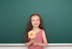 Girl with rose flower near school board Stock Images