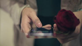 The girl with a rose in hand uses a phone girl writes her boyfriend message. stock footage