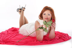 Girl with a rose. Lying on a red background Stock Image