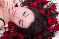 Girl with rose petal in hears. Royalty Free Stock Image