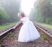 Girl with rose petals. A small girl standing along the railroad track dropping rose petals stock photo