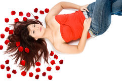 Girl and Rose Petals. A young Asian woman lying on the studio floor with red rose petals Royalty Free Stock Photography
