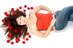 Girl and Rose Petals. A young Asian woman lying on the studio floor with red rose petals Royalty Free Stock Images