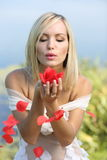 Girl with rose petals. Girl blowing on rose petals and they fly royalty free stock photo
