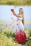 Girl with rose petals. Girl throws rose petals and they fall down, turning in her dress royalty free stock photo