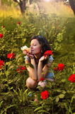 Girl with roses in the garden. Young, happy girl enjoying roses in the garden Stock Photos
