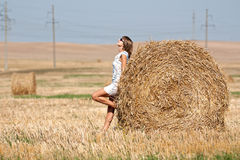 Girl and round haystack Royalty Free Stock Photo