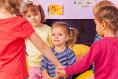 Girl in roundelay circle of friends. Small little girl in the circle of friends play game smile and happy Royalty Free Stock Photos