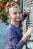 Girl with rowan. Girl near a fence of concrete with a beautiful hairstyle with elements rowan royalty free stock photography