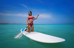 Girl rowing on knees on paddle surf SUP. Girl rowing on her knees on paddle surf board SUP in summer stock photography