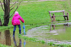 Girl in rubber boots with umbrella walking through the puddles Royalty Free Stock Photography