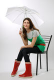 Girl in the rubber boots under an umbrella Stock Photo