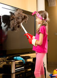 Girl in rubber gloves cleaning big TV from dust with brush Royalty Free Stock Photography
