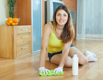 Girl rubbing wooden floor with  cleanser. Girl rubbing wooden floor with rag and cleanser at home Stock Photo