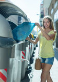 Girl with rubbish near refuse  container Royalty Free Stock Photo