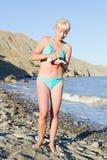 Girl rubs cream sunburn. On the beach Royalty Free Stock Image