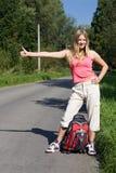 Girl with rucksack. Stops the car Stock Photos