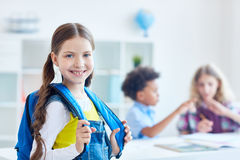 Girl with rucksack. Pretty youngster with rucksack on background of two schoolboys Stock Image