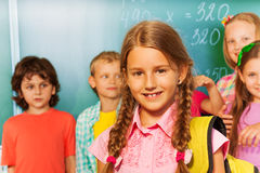 Girl with rucksack on shoulders  near blackboard Royalty Free Stock Image