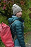 Girl With Rucksack. Vertical shot of a young girl with a rucksack walking in an autumn park Royalty Free Stock Photo