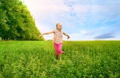 Girl run on green field. Child girl run on green field Royalty Free Stock Photography