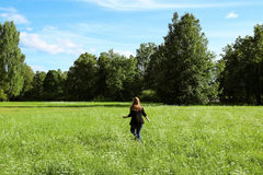 Girl run on the green meadow. Symbol of freedom and clear mind Stock Photo
