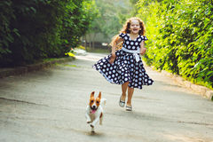 Girl run in a park with a puppy jack russell terrier. Stock Photo