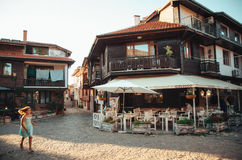 A girl run through streets of ancient nesebar with cafe, resorts, shops at sunset. Stock Images
