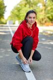 The girl on a run tie her shoelaces on sneakers stock image