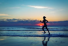 Girl runing  along the sea coast Stock Photography