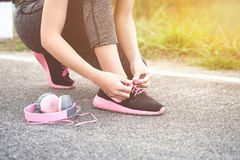 Girl runner tying laces for jogging her shoes on road in a park. stock image