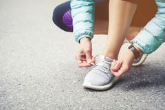 Girl runner tying laces for jogging her shoes on road in a park. Running shoes, Shoelaces. Exercise concept. Sport. Lifestyle. Vintage style stock photo