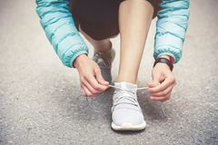 Girl runner tying laces for jogging her shoes on road in a park. Running shoes, Shoelaces. Exercise concept. Sport. Lifestyle. Vintage style stock images