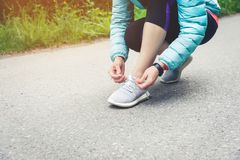 Girl runner tying laces for jogging her shoes on road in a park. Running shoes, Shoelaces. Exercise concept. Sport. Lifestyle. Vintage style royalty free stock images