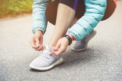 Girl runner tying laces for jogging her shoes on road in a park. Running shoes, Shoelaces. Exercise concept. Sport. Lifestyle. Vintage style stock photography