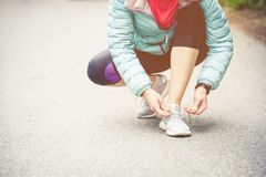 Girl runner tying laces for jogging her shoes on road in a park. Running shoes, Shoelaces. Exercise concept. Sport. Lifestyle. Vintage style royalty free stock image