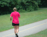 Girl running. A woman runs down a bike/walking path in a recreational park Royalty Free Stock Photos