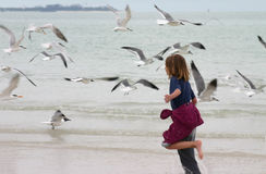 Girl running. Emmi running through the ocean surf with gulls flying Royalty Free Stock Photos