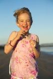 Girl running. A little girl running on the beach at sunset stock photos