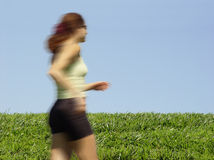 Girl running. Young woman running through the field stock image