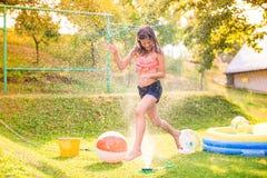 Girl running above a sprinkler, sunny summer back yard Stock Photos
