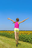 Girl running along the field with sunflowers Royalty Free Stock Photos